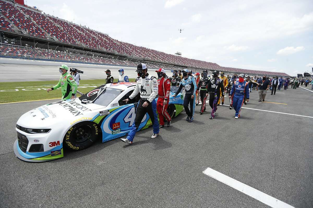 NASCAR drivers push Bubba Wallace's car prior to the start of the NASCAR Cup Series at the Talladega Superspeedway in Talladega, Ala., Monday, June 22, 2020. (AP Photo/John Bazemore)