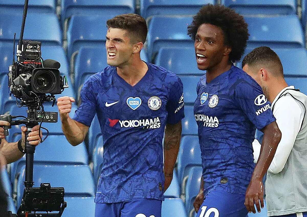 Chelsea's US midfielder Christian Pulisic (L) celebrates scoring the opening goal with Chelsea's Brazilian midfielder Willian during the English Premier League football match between Chelsea and Manchester City at Stamford Bridge in London on June 25, 2020. (Photo by Julian Finney / POOL / AFP)