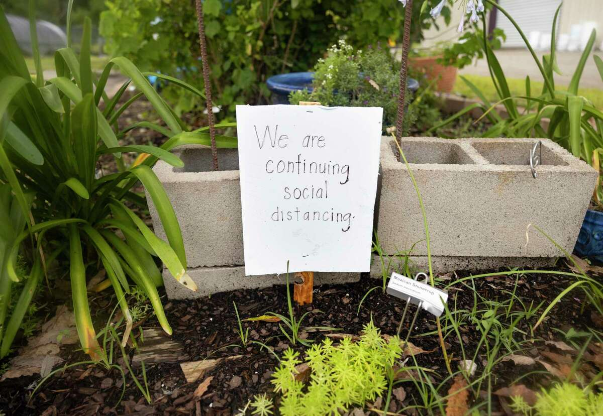 A sign asking visitors to practice social distancing is on display near the Discovery and Children's Garden at the Montgomery County Horticulture, Tuesday, June 23, 2020.