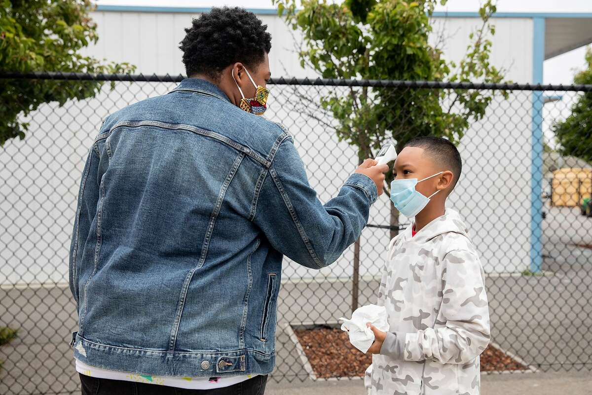 Third grade instructor JayJuan Radford checks a student's temperature as they arrive to attend Freedom School, a six-week summer academic enrichment program for Marin County students held at Bayside Martin Luther King Jr. Academy in Marin City, Calif. Tuesday, June 23, 2020. Sausalito and Marin City schools have implemented safety measures such as temperature checks, providing masks and keeping six feet of distance in order to bring kids back for summer school programs. They hope to bring students back in the fall using these same precautions.