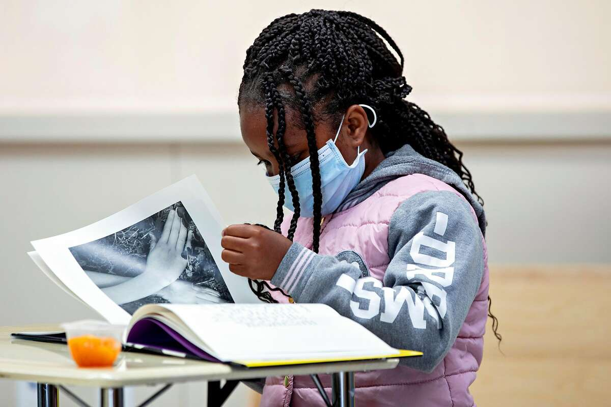 A second grade student wears a mask while reading a book during Freedom School, a six-week summer academic enrichment program for Marin County students held at Bayside Martin Luther King Jr. Academy in Marin City, Calif. Tuesday, June 23, 2020. Sausalito and Marin City schools have implemented safety measures such as temperature checks, providing masks and keeping six feet of distance in order to bring kids back for summer school programs. They hope to bring students back in the fall using these same precautions.