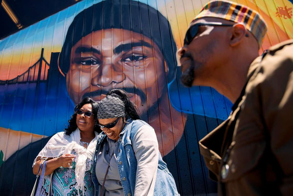 Wanda Johnson (left), mother of the late Oscar Grant, greets a friend while standing underneath a large mural honoring her son during a mural and street naming unveiling for Oscar Grant at Fruitvale BART Station in Oakland, Calif. Saturday, June 8, 2019.