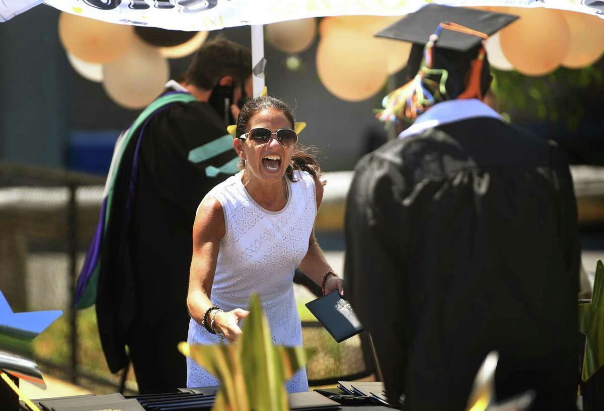 Information Technology Principal Beth Furnari cheers on a graduate as she hands out diplomas during the drive up graduation at the Fairchild Wheeler Interdistrict Magnet High Schools campus in Bridgeport, Conn. on Thursday, June 25, 2020.