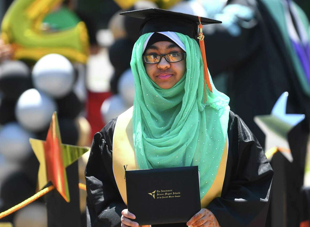 Graduates pick up their diplomas during the drive up graduation at the Fairchild Wheeler Interdistrict Magnet High Schools campus in Bridgeport, Conn. on Thursday, June 25, 2020.