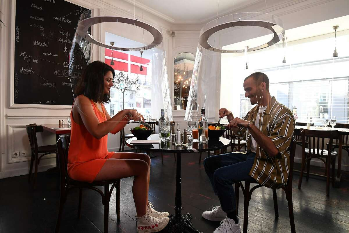 In this file photo taken on May 27, 2020 a couple has a lunch under plexiglass protection designed by Christophe Gernigon at the H.A.N.D restaurant in Paris, as France eased lockdown measures taken to curb the spread of the COVID-19 pandemic, caused by the novel coronavirus.