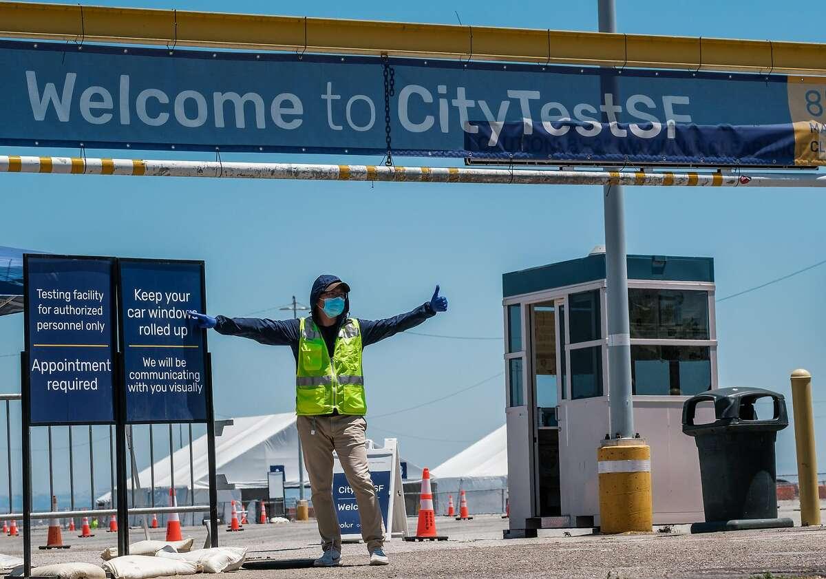 An attendant motions towards a car entering Coronavirus testing site at Pier 30 in San Francisco on Thursday, June 25, 2020.