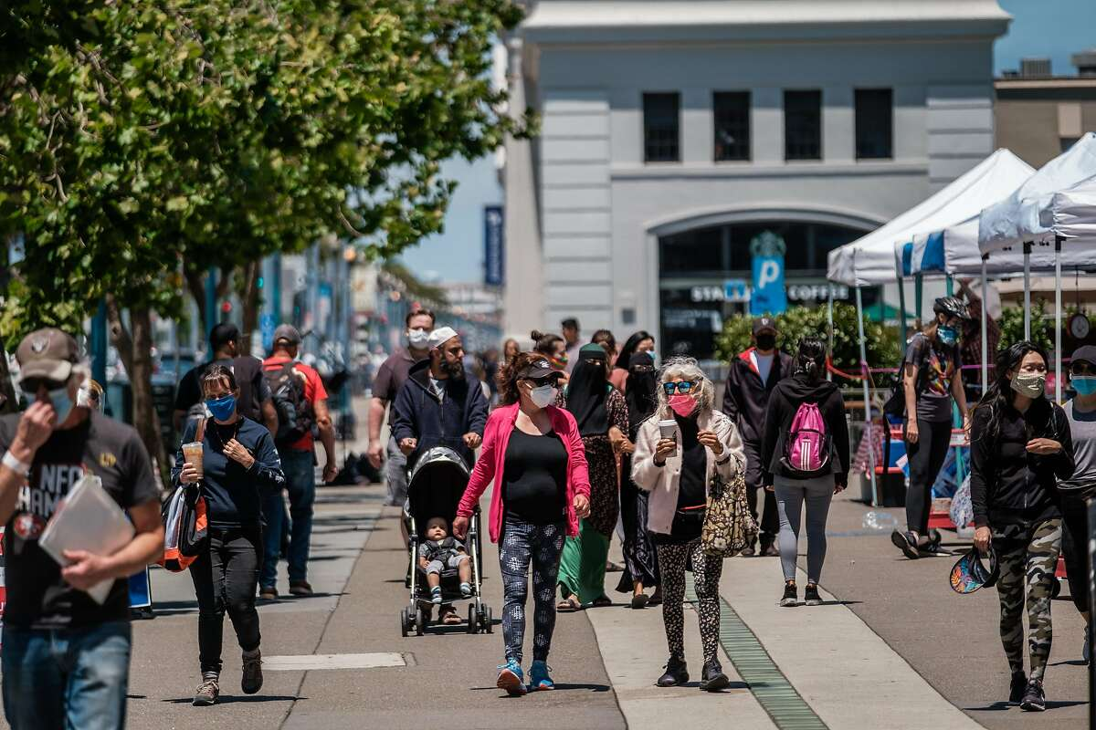 People are seen along the Embarcadero in San Francisco on Thursday, June 25, 2020.