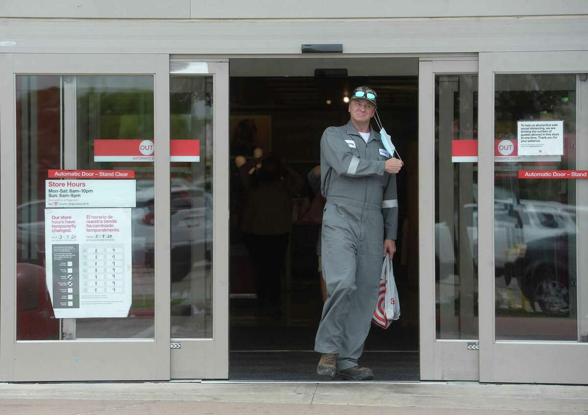 A shopper removes his mask after making his way out of the Target store in Port Arthur on the first day of a new ordinance issued by Jefferson County Judge Jeff Branick requiring everyone to wear masks while at businesses. The order went into effect noon Wednesday. Photo taken Wednesday, June 24, 2020 Kim Brent/The Enterprise