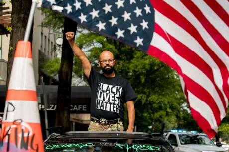 George Floyd's name is written on the windshield as John Coy wears a shirt that reads Black Lives Matter and stands through his sunroof with his fist in the air at 16th Street Northwest renamed Black Lives Matter Plaza near the White House, Friday, June 19, 2020, in Washington.