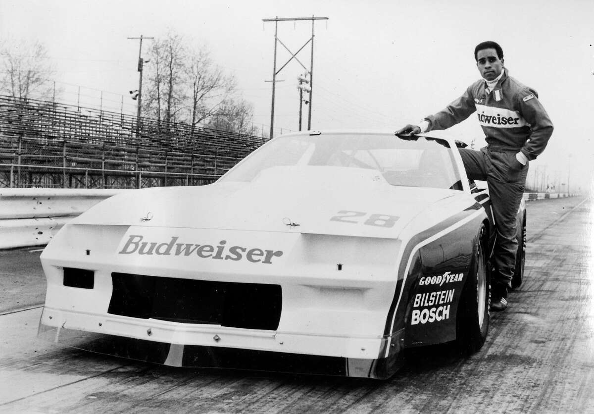 A half length portrait of racing driver Willy T Ribbs, a member of the Budweiser Trans Am team, standing next to his racing car, 1980.