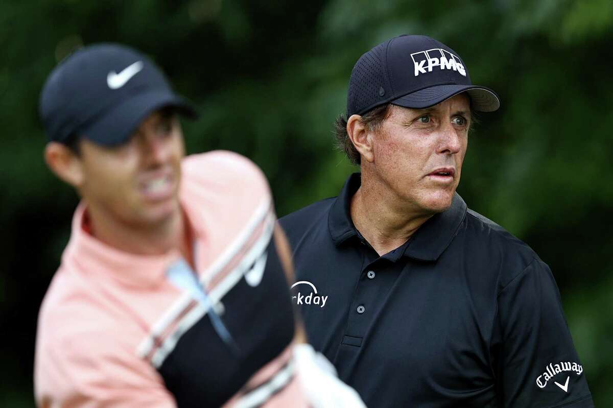 CROMWELL, CONNECTICUT - JUNE 25: Rory McIlroy of Northern Ireland and Phil Mickelson of the United States react on the 12th tee during the first round of the Travelers Championship at TPC River Highlands on June 25, 2020 in Cromwell, Connecticut. (Photo by Elsa/Getty Images)