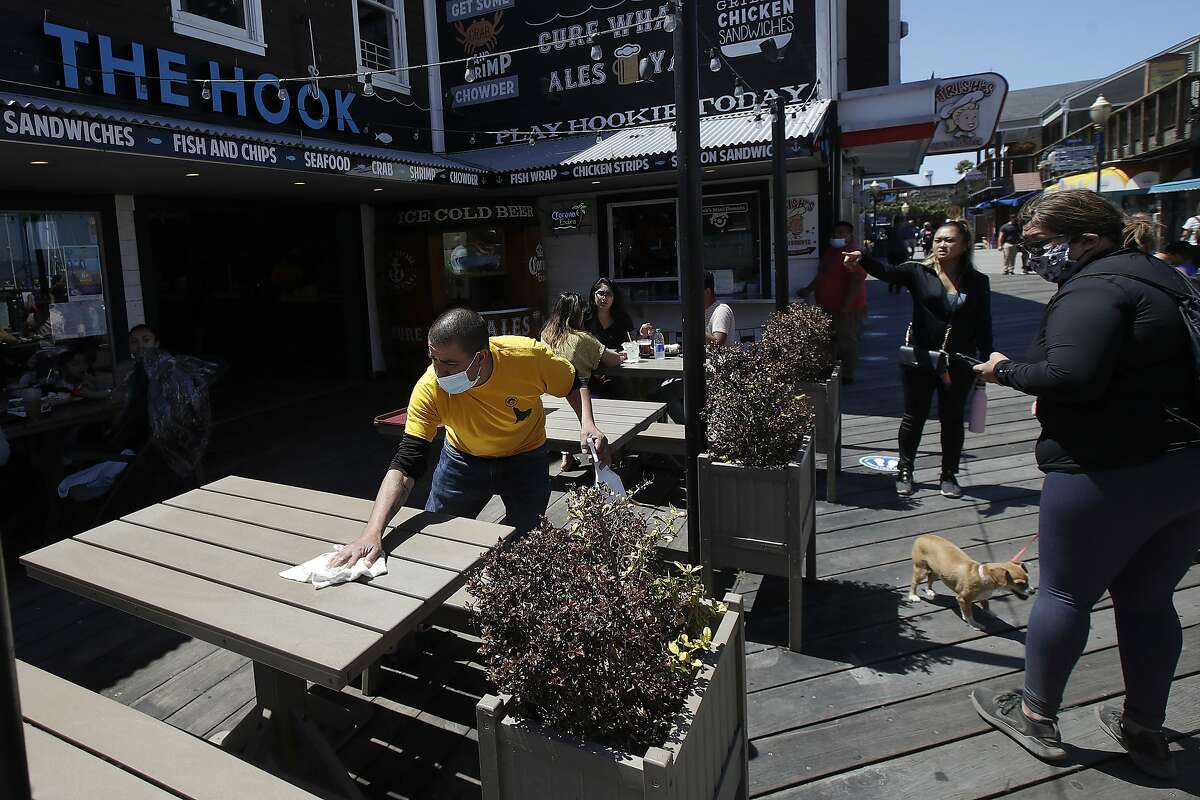 FILE - In this June 18, 2020, file photo, a man wears a face mask while cleaning an outdoor dining table at Pier 39 where some stores, restaurants and attractions have reopened during the coronavirus outbreak in San Francisco.