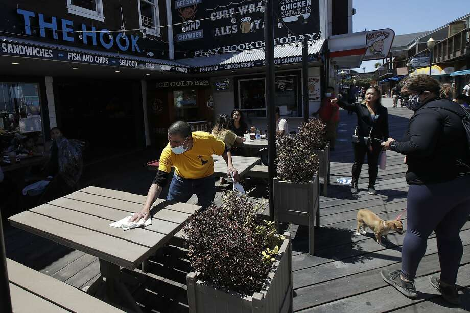 FILE - In this June 18, 2020, file photo, a man wears a face mask while cleaning an outdoor dining table at Pier 39 where some stores, restaurants and attractions have reopened during the coronavirus outbreak in San Francisco. Photo: Jeff Chiu, Associated Press