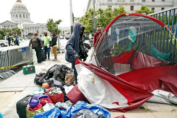 DJ and Ashley Haynes take down their tent on McAllister Street while being relocated to a shelter in place hotel in San Francisco, Calif., on Friday, June 12, 2020.