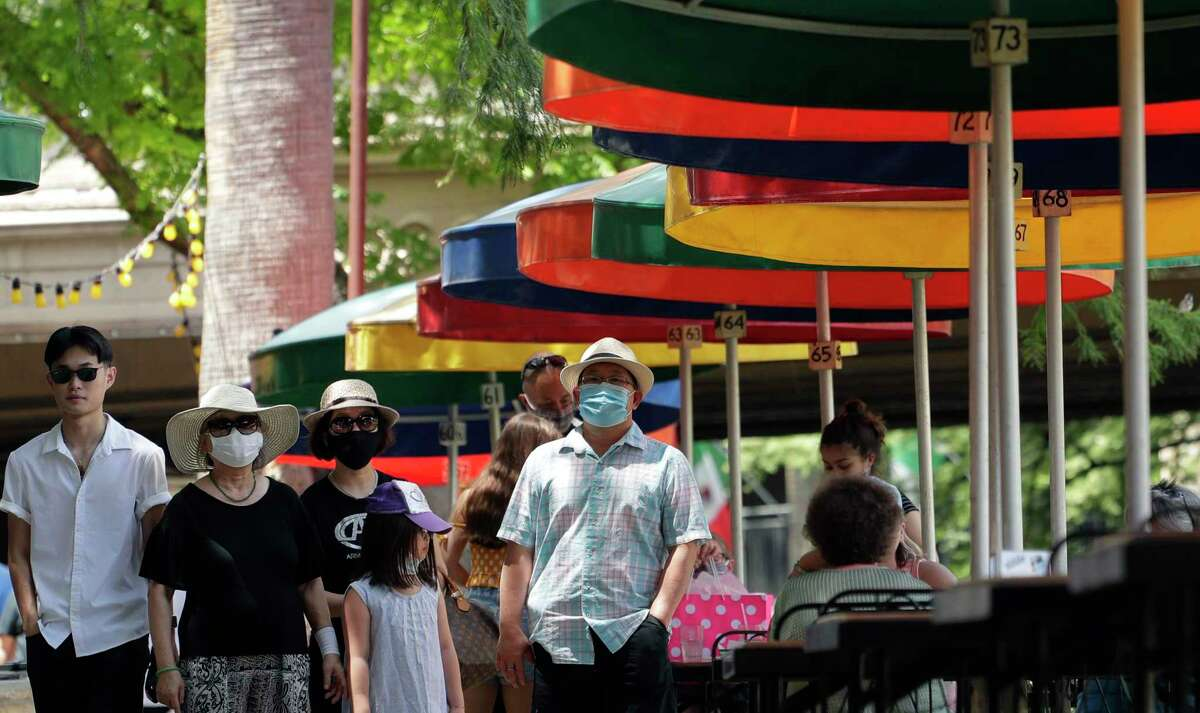 Visitors, some wearing masks to protect against the spread of COVID-19, walk along the River Walk in San Antonio, Wednesday, June 24, 2020, in San Antonio. Cases of COVID-19 have spiked in Texas and the governor of Texas is encouraging people to wear masks in public and stay home if possible. (AP Photo/Eric Gay)