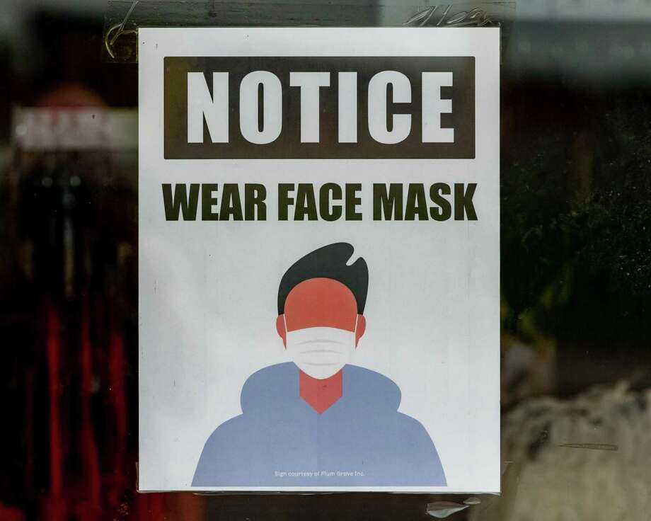 About a half dozen signs are posted near the entrance to the Rainbow apparel shop in the North Park Plaza to let shoppers know that masks are required for shopping in the store. Photo made on June 24, 2020. 