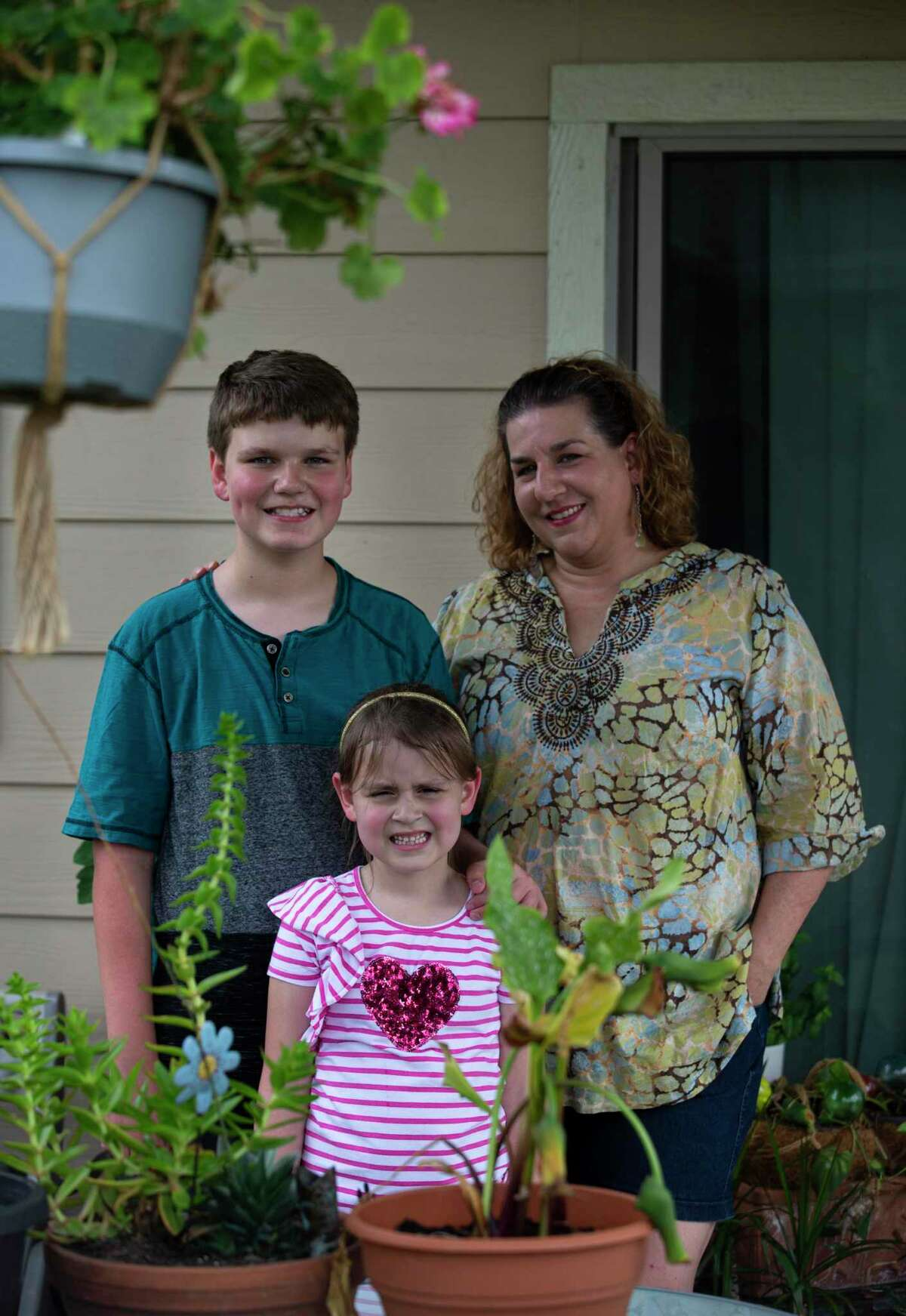 Denise Cupit and her two children, Riley Cupit, 11, and Zoey Cupit, 6, pose for a photograph Thursday, June 25, 2020, at their backyard in Katy. Riley will be going to sixth grade and Zoey will be going to first grade in Katy ISD, but Denise said they are not likely to return until community spread is practically zero, or until there's a widely available and safe vaccine.