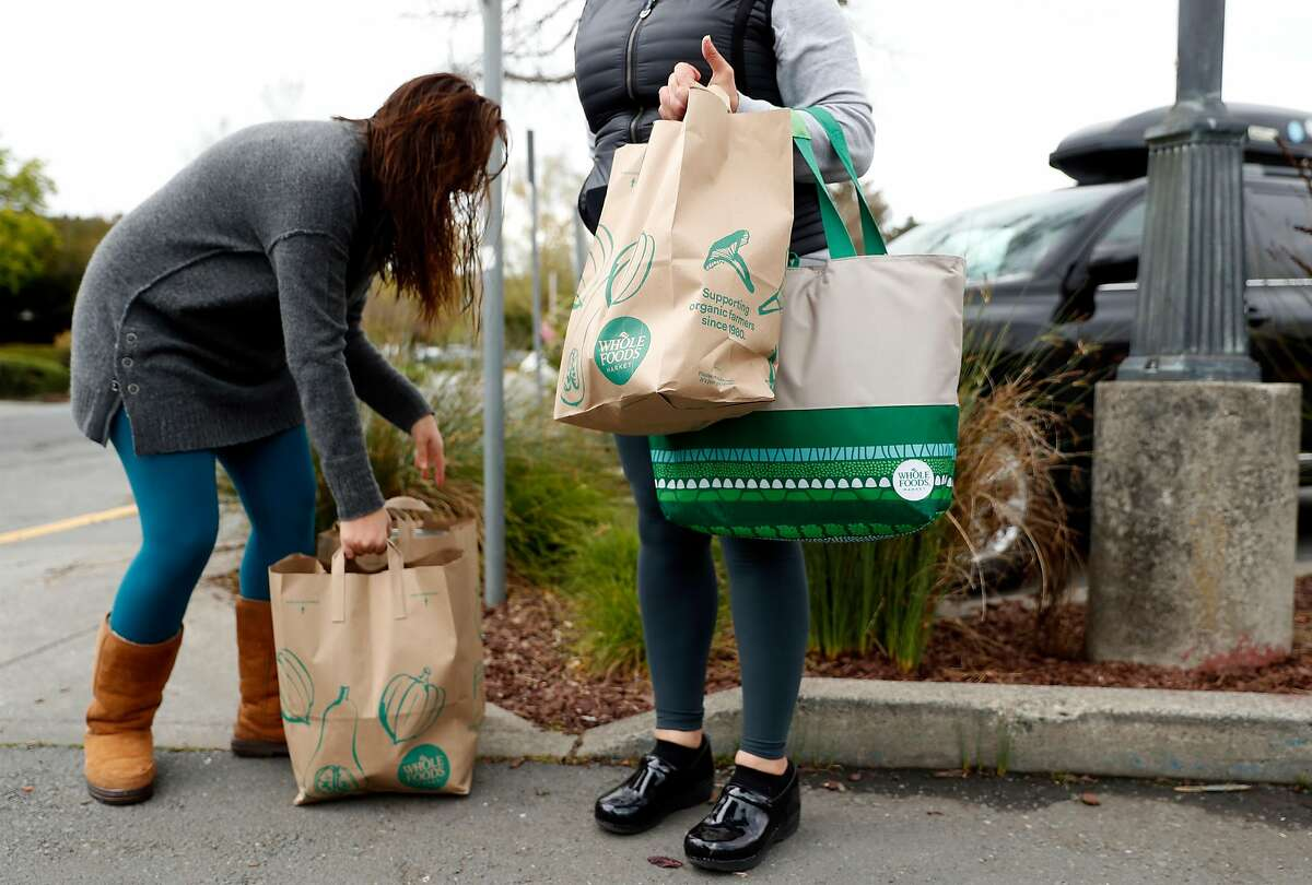 After not being able to use their own bags, Bertha Iavorone and her daughter, Rebeca, leave with store provided paper bags after shopping at Whole Foods in Mill Valley, Calif., on Monday, April 6, 2020.