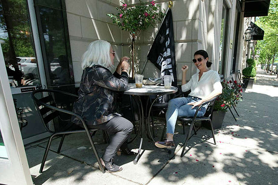 People chat with each while social distancing outside a coffee shop in Winnetka. Gatherings of up to 50 people will be allowed across the state starting today as Illinois moves into the fourth phase of its reopening plan. For Phase 4, restaurants also can seat parties of up to 10 people for indoor dining and drinking. Photo: Nam Y. Huh | AP