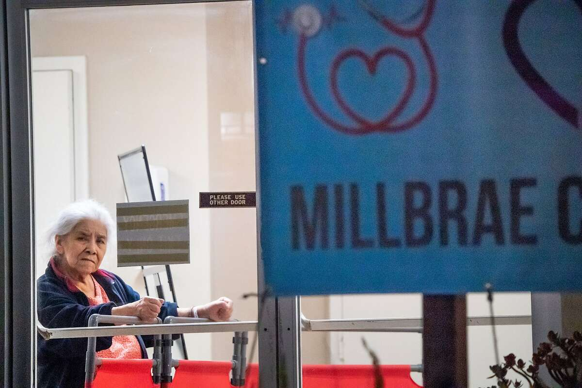 A resident in her 70's is at the front doors of the Millbrae Skilled Care on Thursday, June 25, 2020 in San Mateo, Calif. The facility had one of the biggest outbreaks of the coronavirus within the county with over 100 people infected and 16 dead.