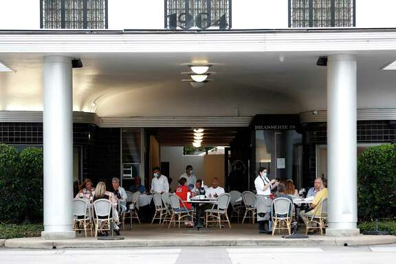 People dine and hang out on the patio of Brasserie 19 on West Gray Street, Thursday, June 25, 2020, in Houston.