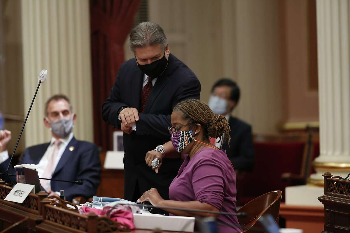 Sen. Holly Mitchell, D-Los Angeles, chair of the Senate Budget and Fiscal Review Committee, gets an elbow bump from Sen. Robert Hertzberg, D-Los Angeles, after the Senate approved the $202.1 billion state budget at the Capitol in Sacramento, Calif., Thursday, June 25, 2020. Mitchell carried the bills that made up the spending plan that covers the state's estimated $54.3 billion deficit brought on by the coronavirus. The Assembly is scheduled to vote on the budget Friday. (AP Photo/Rich Pedroncelli)