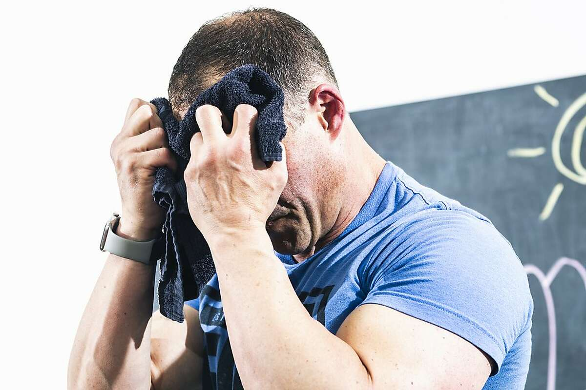J.J. Miller, founder of The Firm Fitness, wipes away perspiration while leading a fitness class over Zoom on Wednesday, June 10, 2020 in San Francisco, California.