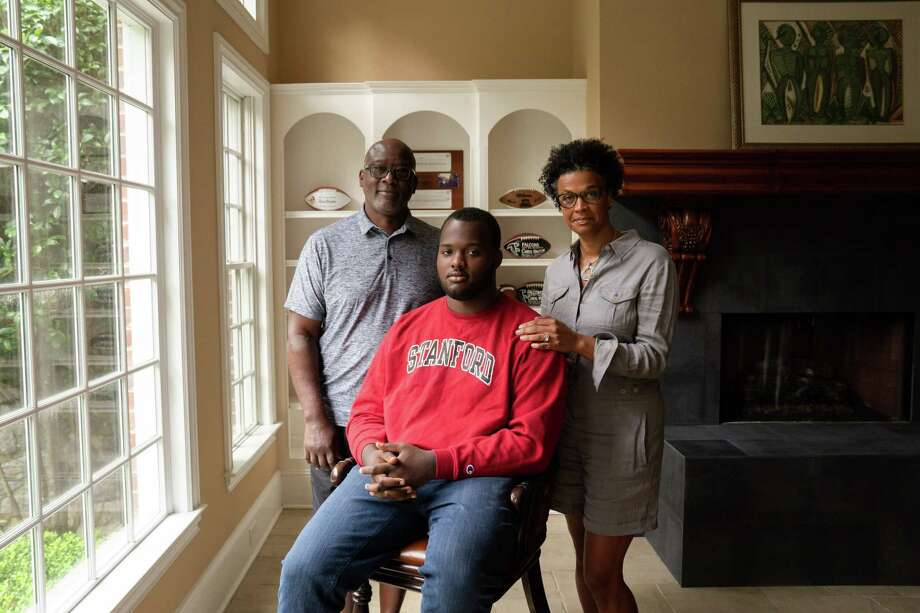 Chris, left, and Mya Hinton, right, pictured with their son Myles in their Atlanta home, formed an advocacy group for parents of college football players. Photo: Photo For The Washington Post By Kevin D. Liles / Kevin D. Liles