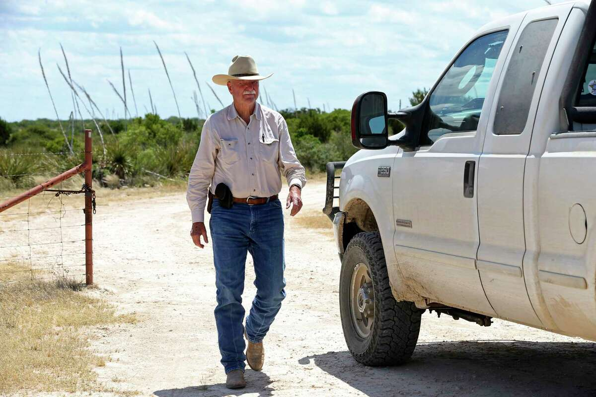 Dickinson heads back to his truck after opening a gate while heading to his house at the Skyline Ranch.