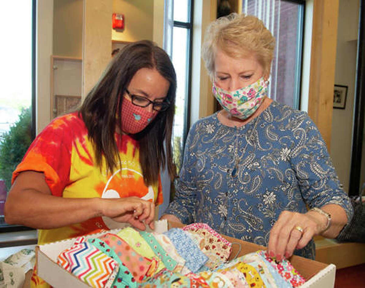 SIUE ECC teacher Stephanie Henschen, left, looks through some of the masks longtime ECC friend and retired Edwardsville teacher Kathy Weber made for ECC staff.