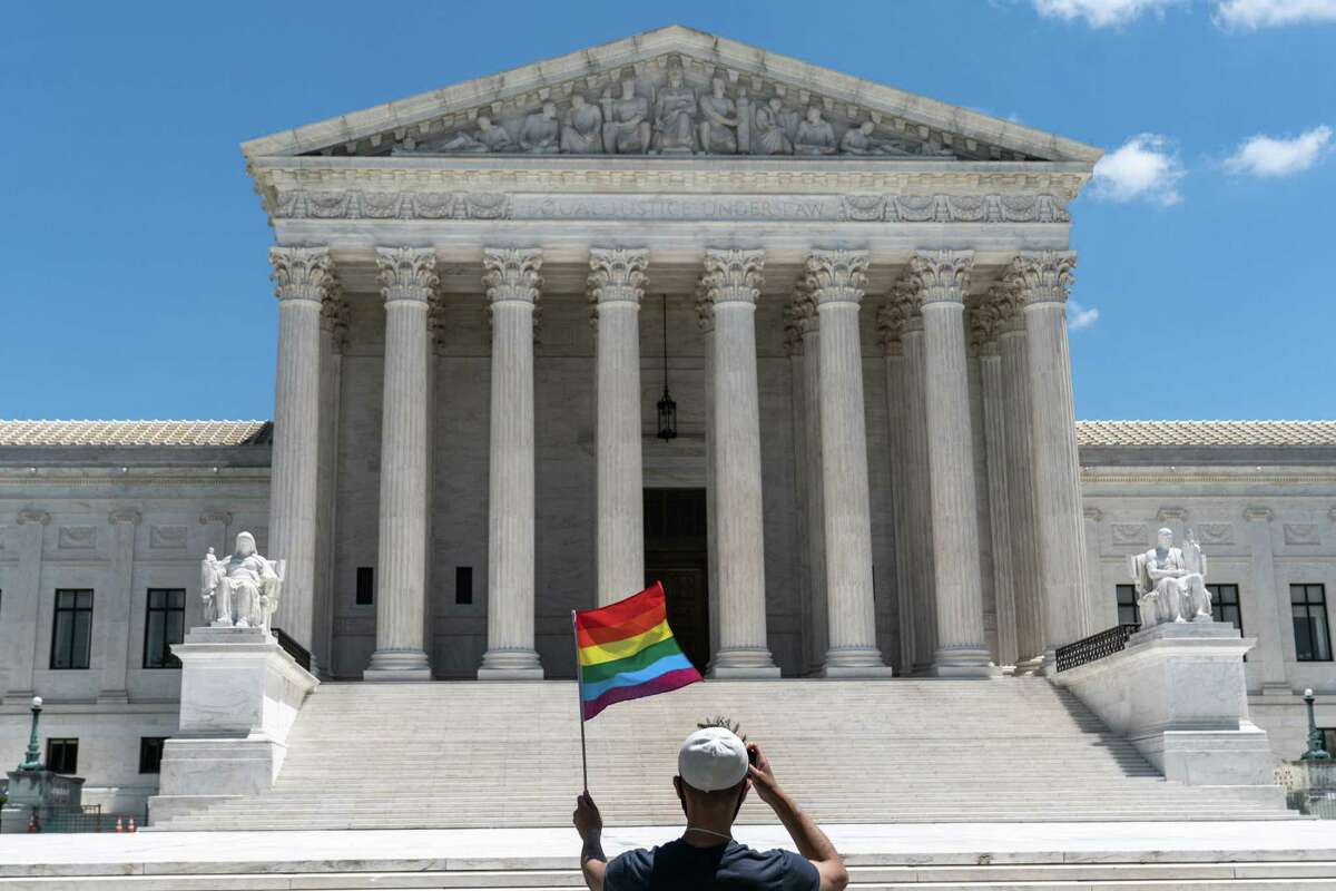 A person waves a rainbow flag in front of the Supreme Court in Washington, on Monday, June 15, 2020. The Supreme Court ruled Monday that a landmark civil rights law protects gay and transgender workers from workplace discrimination, handing the movement for LGBTQ equality a stunning victory. (Anna Moneymaker/The New York Times)