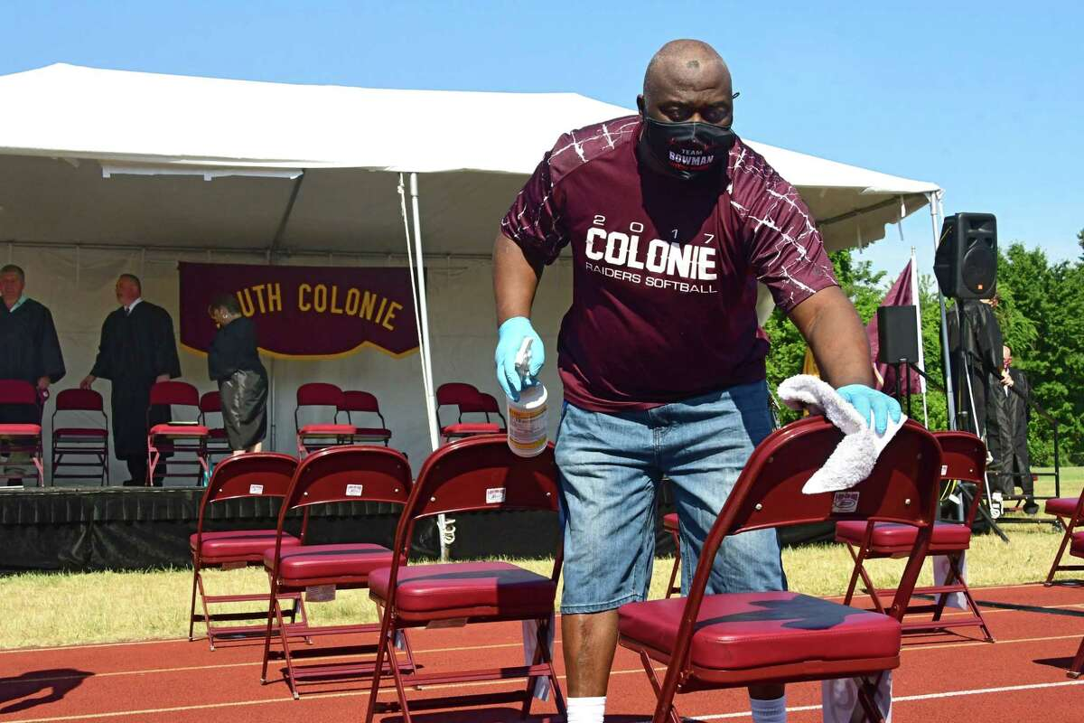 School custodian Robert Bowman disinfected chairs between sessions where graduates were seated as Colonie Central High School holds graduation for seniors on their football field on Friday, June 26, 2020 in Colonie, N.Y. (Lori Van Buren/Times Union)