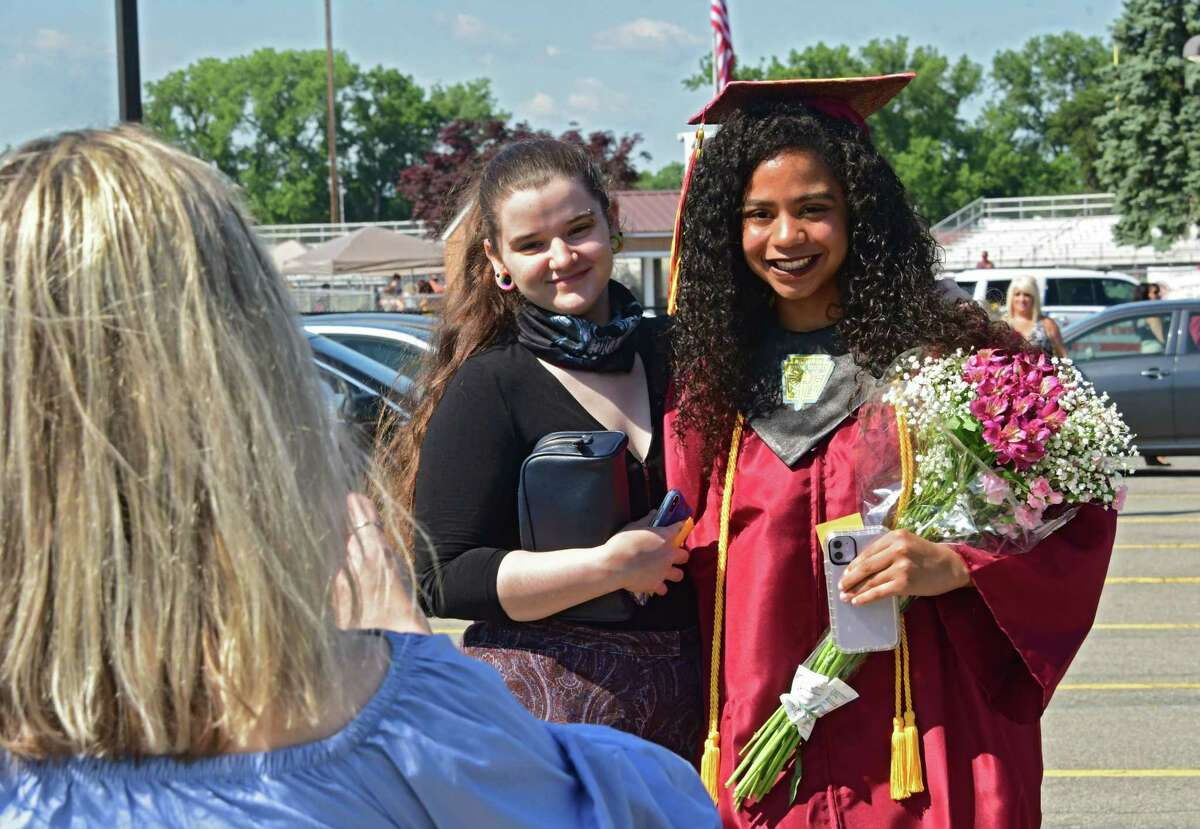 Quianna Saunders, left, takes a photo of her daughters Tyffanie Saunders, center, and graduate Jasmine Edmonds as Colonie Central High School holds graduation for seniors on their football field on Friday, June 26, 2020 in Colonie, N.Y. (Lori Van Buren/Times Union)