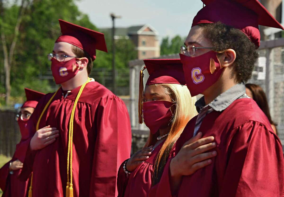 Graduates stand for the National Anthem as Colonie Central High School holds graduation for seniors on their football field on Friday, June 26, 2020 in Colonie, N.Y. (Lori Van Buren/Times Union)