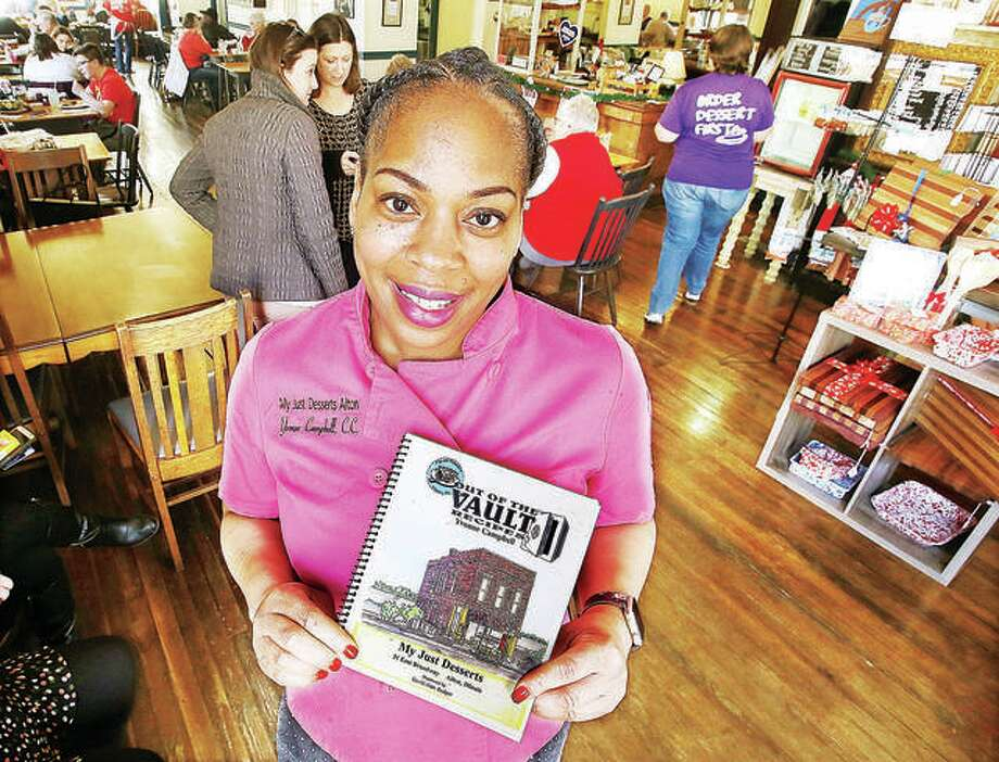 """In this December 2018 file photo, Yvonne Campbell, owner of My Just Desserts, 31 E. Broadway, in Alton, holds the cookbook she wrote called """"Out of the Vault Recipes."""" Campbell accepted a deal with McAlister's Deli, in Edwardsville, which help her avoid a potential financial crisis. The deal has been about spreading awareness through a campaign promoted by McAlister's called Love Your Neighbor, which seeks to find local, black-owned businesses to help spread a message of unity Photo: John Badman 