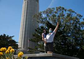Mariposa Villaluna stands on a pedestal with their 4-year-old child in the parking lot at Coit Tower in San Francisco, Calif. on Thursday, June 18, 2020 after a crew from the city dismantled a statue of Christopher Columbus during the night.