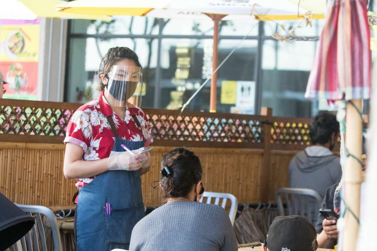 Waitress Jariya Namwaan takes a customer's orders while working a shift at Farmhouse Kitchen in Oakland, Calif. on June 23, 2020. The restaurant recently re-opened to customers for outdoor dine-in service.