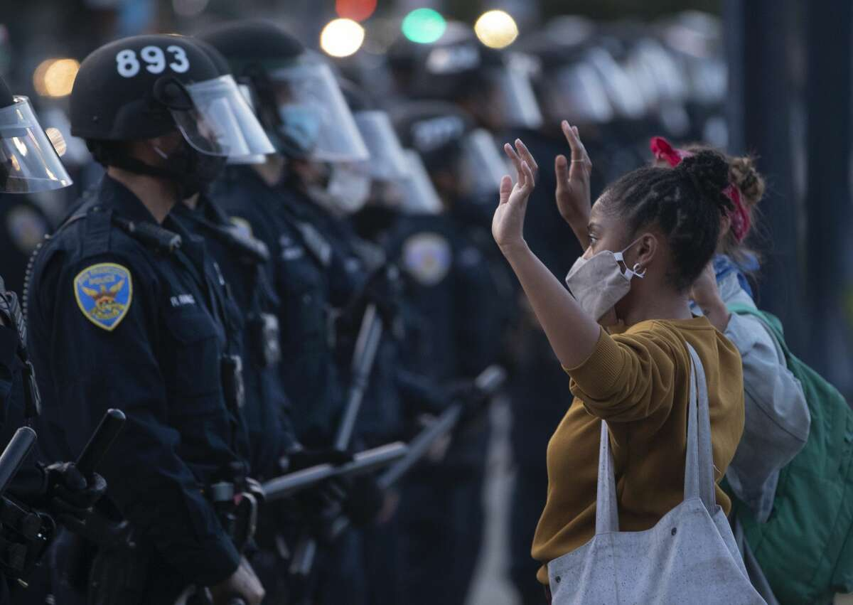 FILE - With her hands raised, a woman faces off against San Francisco police as they push people away from City Hall after the 8 PM curfew went into effect, Sunday, May 31, 2020, the third day of Bay Area unrest over the George Floyd killing in Minneapolis. The city recently released data on curfew arrests made between May 31 to June 4.