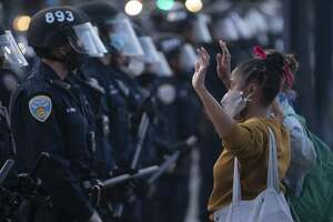 SAN FRANCISCO, CA - MAY 31: With her hands raised, a woman faces off against San Francisco police as they push people away from City Hall after the 8 PM curfew went into effect, Sunday, May 31, 2020, the third day of Bay Area unrest over the George Floyd killing in Minneapolis. (Karl Mondon/Digital First Media/East Bay Times via Getty Images)