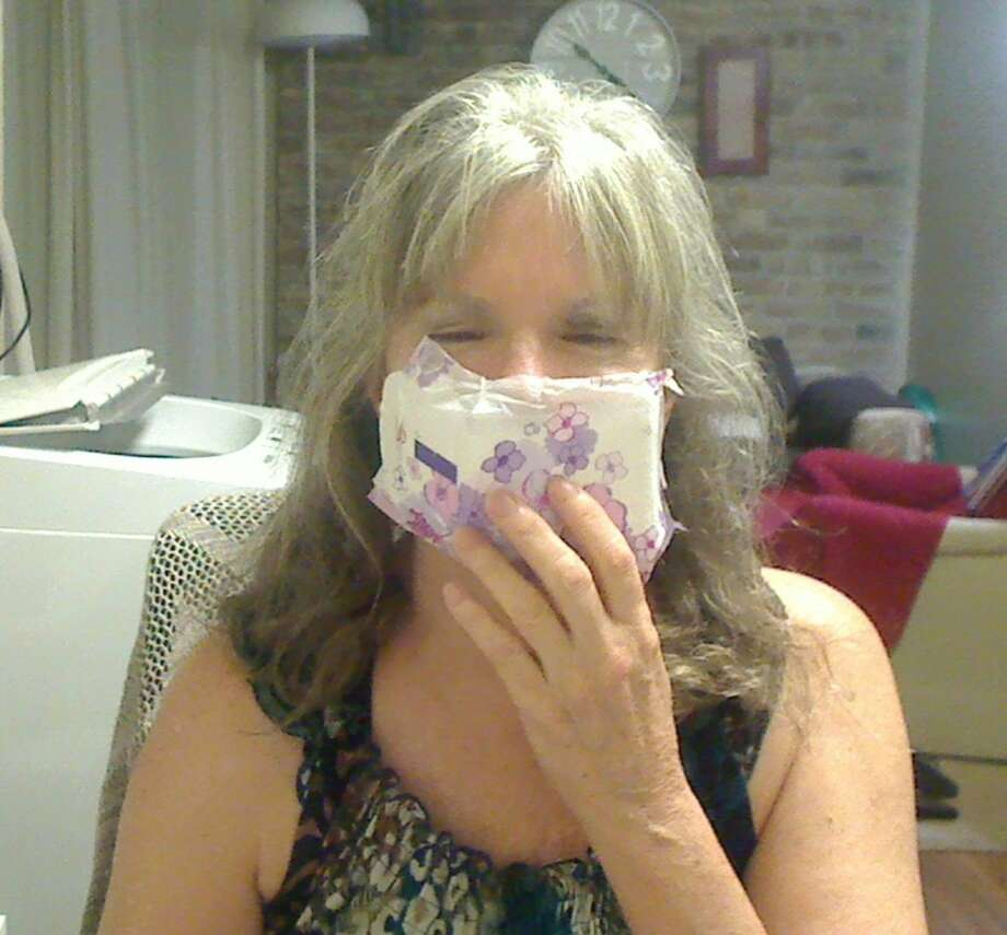 """Robin Berkley unknowingly became the subject of a popular Facebook post on Thursday during a trip to the U.S Post Office near the San Antonio International Airport.A fellow customer noticed Berkley's improvised mask — a sanitary pad — and snapped a quick photo of her at the counter for a lighthearted Facebook post showing """"you gotta do what you gotta do"""" as COVID-19 continues to spread at increased rates throughout Texas. Photo: Courtesy, Natalie Charlene"""
