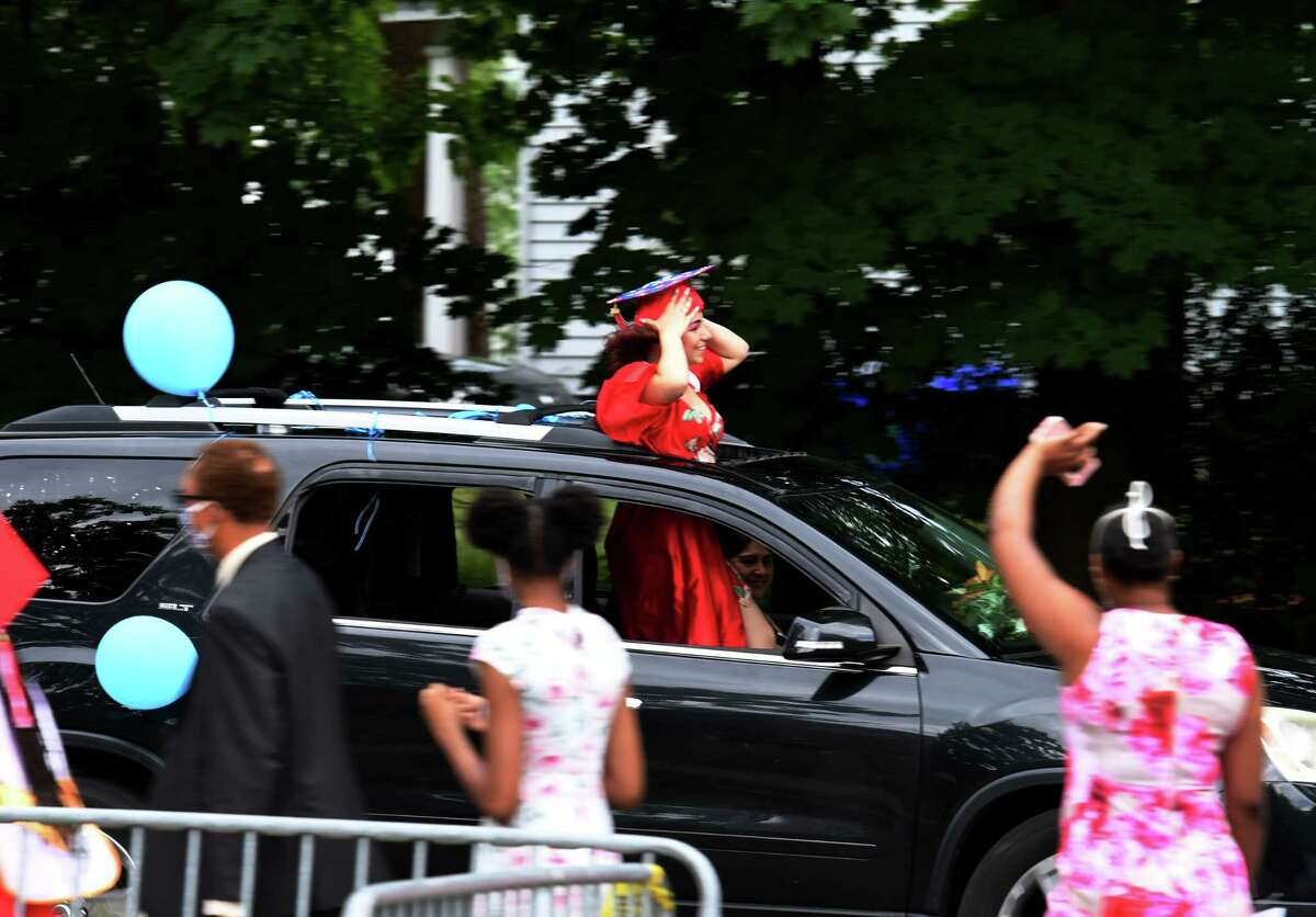 Thearse McCalmon, right, waves at a celebrating Schenectady High School graduate after attending her daughter's commencement on Friday, June 26, 2020, in Schenectady, N.Y. McCalmon just secured the Democratic nomination for the 49th State Senate District race against incumbent James Tedisco. (Will Waldron/Times Union)