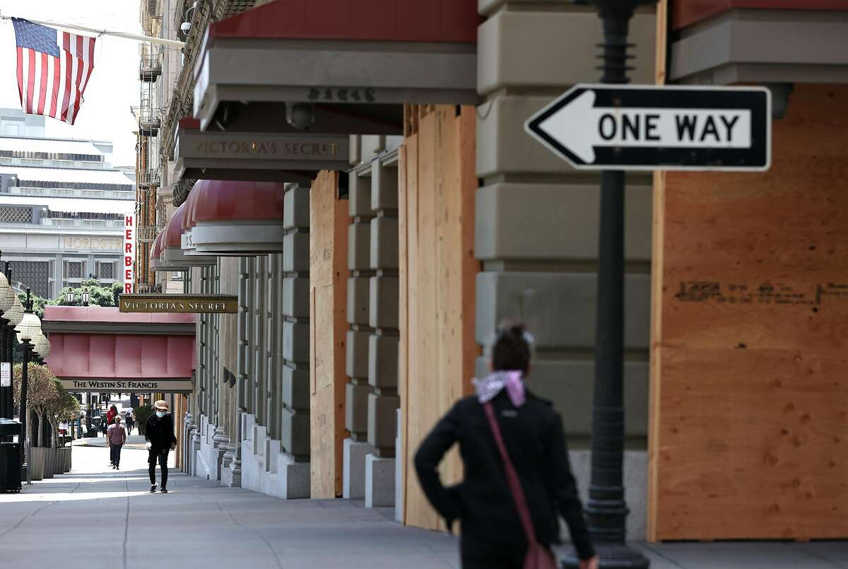 SAN FRANCISCO, CALIFORNIA - JUNE 11: Pedestrians walk by boarded up businesses on June 11, 2020 in San Francisco, California. Economic worries due to the coronavirus COVID-19 pandemic continue as an additional 1.5 million people filed for first-time unemployment benefits in the past week. The Dow Jones Industrial average plunged over 1,800 points on the news. (Photo by Justin Sullivan/Getty Images)