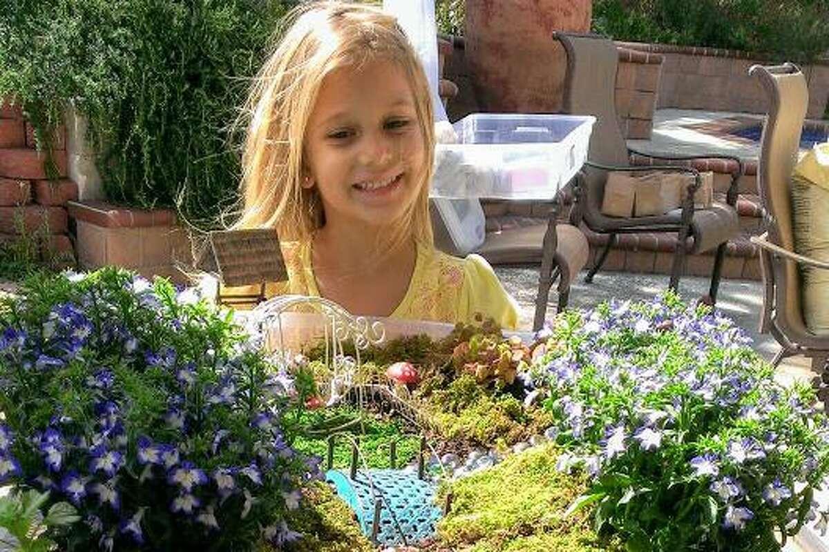 Stefanie Vodrazka admires a fairy garden created at a birthday party hosted by San Antonio Charter Moms member Iris Gonzalez.