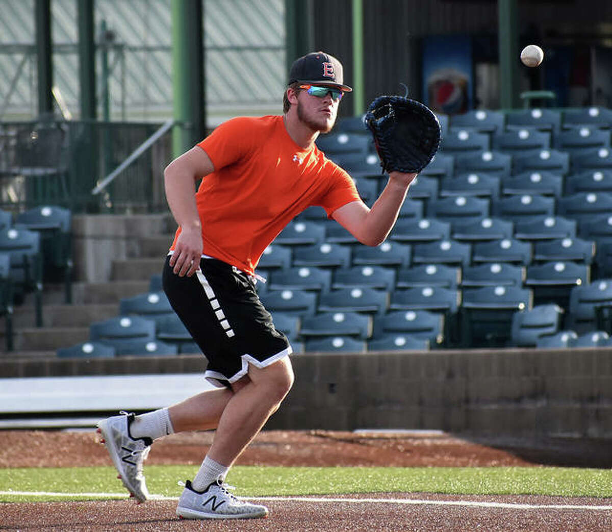 Edwardsville's Gavin Reames fields a ground ball at first base during an infield drill at Tuesday's practice inside GCS Stadium in Sauget.