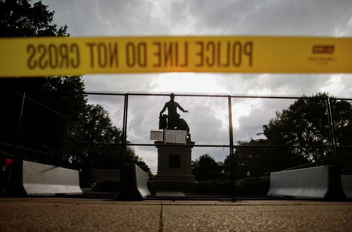 Yellow police tape, concrete barricades and fencing surround the Emancipation Memorial in Lincoln Park in Washington June 25. The Emancipation Memorial depicts a freed slave kneeling at the feet of President Abraham Lincoln. Calls are intensifying for the removal of the statue as the nation confronts racial injustice.