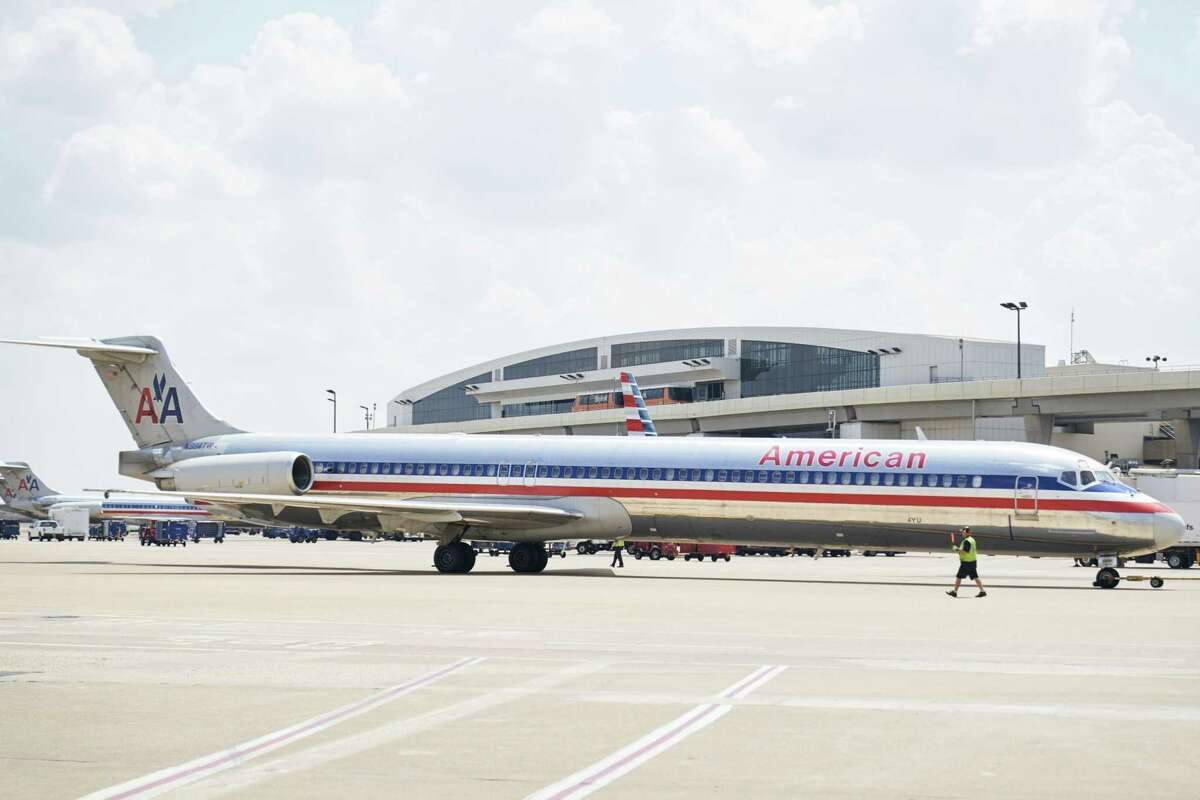 An airport worker guides an American Airlines MD-80 aircraft to a gate at Dallas/Fort Worth International Airport in Texas, on Sept. 1, 2019.