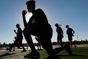 Athletes stretch during a strength and conditioning camp at Grand Oaks High School, Thursday, June 11, 2020, in Spring.