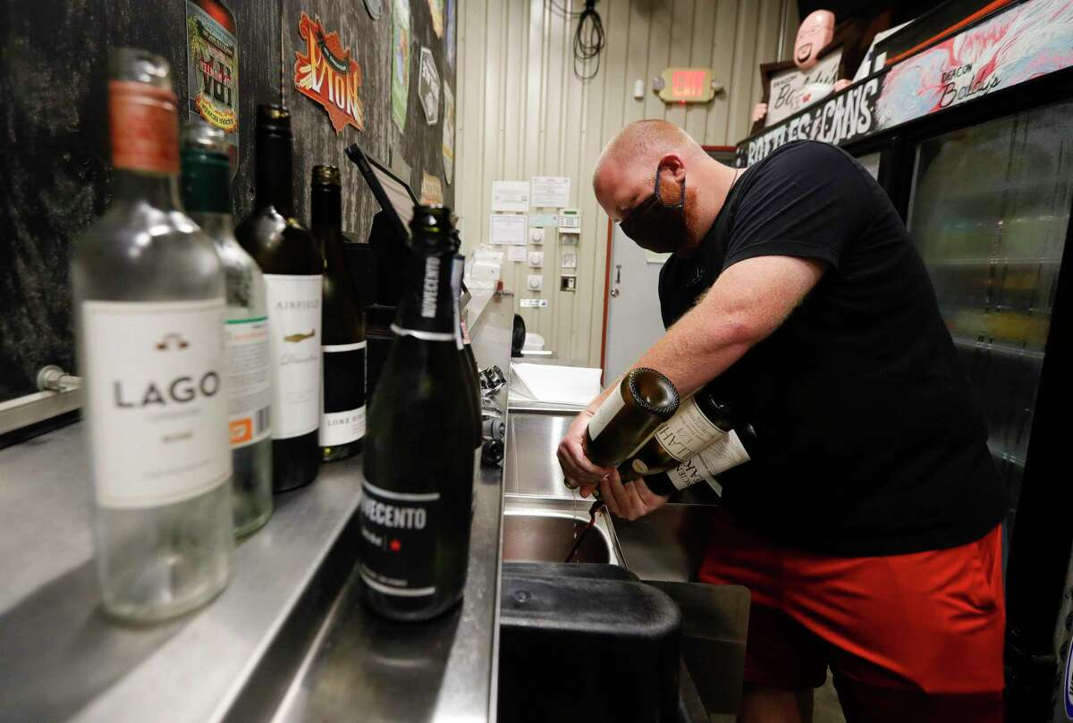 General manager Joey Muckenthaler pours opened bottles of wine down the drain at Deacon Baldy's Bar after Gov. Greg Abbott ordered bars to close as of noon, Friday, June 26, 2020, in Magnolia.