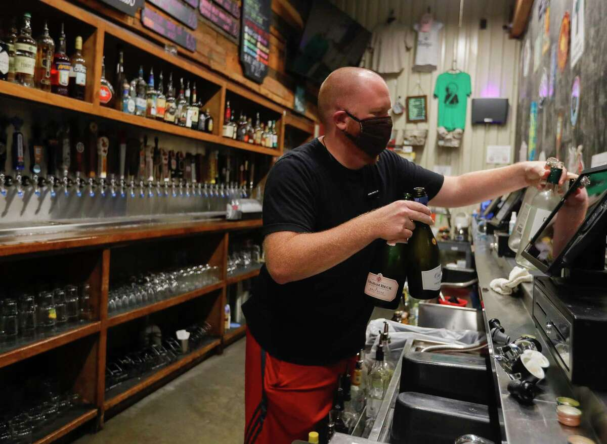 General manager Joey Muckenthaler gathers bottles of wine to pour down the drain at Deacon Baldy's Bar after Gov. Greg Abbott ordered bars to close as of noon, Friday, June 26, 2020, in Magnolia.