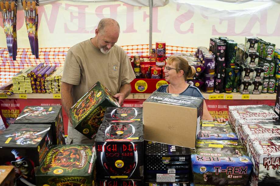 Midland residents Teri Johnson, right, and Troy Kerns, left, shop for fireworks Friday, June 26, 2020 at the Jake's Fireworks tent near the intersection of Patrick Road and Washington Street. (Katy Kildee/kkildee@mdn.net) Photo: (Katy Kildee/kkildee@mdn.net)